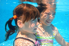 Happy girls swim underwater in pool Stock Image