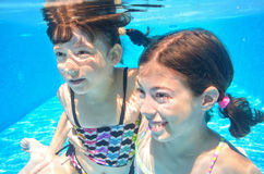 Happy girls swim underwater in pool Royalty Free Stock Photography