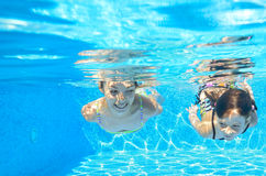 Happy girls swim underwater in pool Royalty Free Stock Image