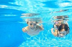 Happy girls swim underwater in pool Royalty Free Stock Image