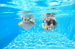 Happy girls swim underwater in pool Royalty Free Stock Photos