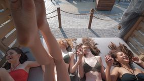 Happy girls in swimsuits with beautiful bodies on sea holidays have fun jumping into bungalows on coast during summer