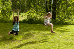 Happy girls on swings Stock Image