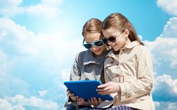 Happy girls with tablet pc computer over blue sky Stock Image