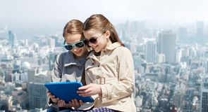 Happy girls with tablet pc computer over city Royalty Free Stock Image