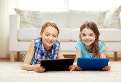 Happy girls with tablet pc lying on floor at home. People, children, technology, friends and friendship concept - happy little girls with tablet pc computers Stock Image