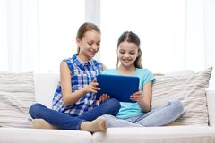 Happy girls with tablet pc sitting on sofa at home Royalty Free Stock Photo