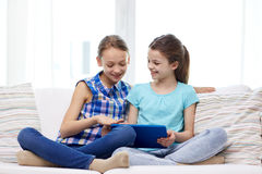 Happy girls with tablet pc sitting on sofa at home Stock Image