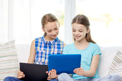 Happy girls with tablet pc sitting on sofa at home. People, children, technology, friends and friendship concept - happy little girls with tablet pc computers Royalty Free Stock Images