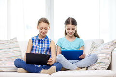 Happy girls with tablet pc sitting on sofa at home Royalty Free Stock Photography