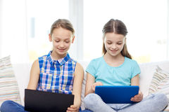 Happy girls with tablet pc sitting on sofa at home Royalty Free Stock Photos