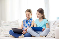Happy girls with tablet pc sitting on sofa at home. People, children, technology, friends and friendship concept - happy little girls with tablet pc computers Royalty Free Stock Photos