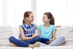 Happy girls with tablet pc talking at home. People, children, technology, friends and friendship concept - happy little girls with tablet pc computer sitting on Royalty Free Stock Photo