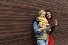 Happy girls with take away coffee outdoors stock images