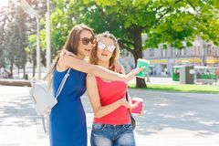 Happy girls with take away coffee outdoors. Outdoors portrait of two female friends. Girls in casual summer outfits having city walk, drinking take away coffee Royalty Free Stock Image