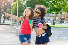 Happy girls with take away coffee outdoors. Outdoors portrait of two female friends. Multiethnic girls in casual summer outfits having city walk, drinking take Royalty Free Stock Image
