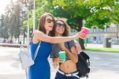 Happy girls with take away coffee outdoors. Outdoors portrait of two female friends. Multiethnic girls in casual summer outfits having city walk, drinking take Royalty Free Stock Photography