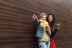 Happy girls with take away coffee outdoors. Outdoors portrait of two female friends. Girls in casual warm outfits having city walk in cold season, drinking Stock Photo