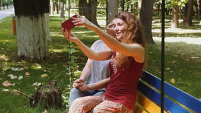 Happy girls taking selfie with the smartphone on a bench in the park. 4k stock video