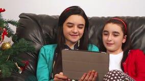 Happy girls talking online near Christmas tree stock footage