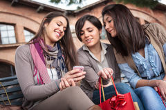 Happy girls texting after shopping Royalty Free Stock Images