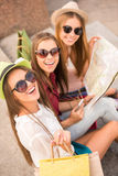 Happy Girls. Three beautiful young women walk in the city, using a map, outdoors Stock Photography