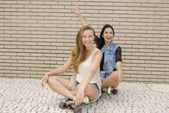 Happy girls. Two beautiful and young girlfriends having fun with a skateboard Stock Photography