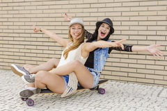 Happy girls. Two beautiful and young girlfriends having fun with a skateboard, in front of a brick wall Stock Photos