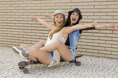 Happy girls. Two beautiful and young girlfriends having fun with a skateboard, in front of a brick wall Royalty Free Stock Image