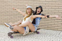 Happy girls. Two beautiful and young girlfriends having fun with a skateboard, in front of a brick wall Royalty Free Stock Photo