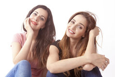 Happy girls. Two happy smiling girls sitting around in casual pose Stock Photo