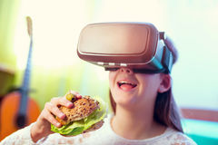 Happy girls in virtual reality glasses eating sandwich Stock Images