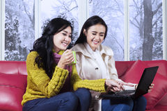 Happy girls in warm clothes using laptop. Portrait of cheerful girls wearing warm clothes and sitting on sofa while using laptop together at home in winter day Stock Photo