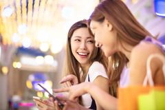 Girls watching phone in the shopping mall. Happy girls watching phone in the shopping mall Royalty Free Stock Image