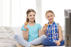 Happy girls watching tv and eating cookies at home. People, children, television, friends and friendship concept - two happy little girls watching tv and eating Stock Images