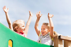 Happy girls waving hands on children playground Stock Photo
