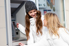 Happy girls withdrawing money Royalty Free Stock Photos
