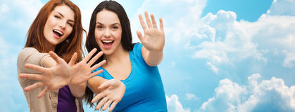 Happy girls or young women showing their palms. Happiness and people concept - two smiling girls or young women showing their palms over blue sky with clouds royalty free stock images