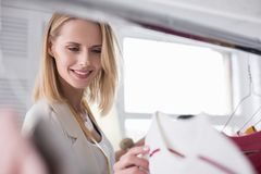 Happy glad businesswoman scrutinizing garments. Fashion business. Low angle of attractive vigorous businesswoman putting garment on stand while gazing down Stock Images