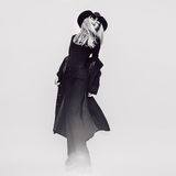 Happy Glamorous lady in a black coat and hat. Black and white vi Royalty Free Stock Photo