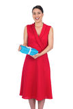 Happy glamorous model in red dress holding present Royalty Free Stock Images