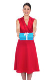 Happy glamorous model in red dress offering present Royalty Free Stock Images