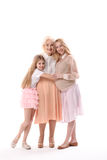Happy glances of female relatives. Pregnant mother with her daughter are hugging eldest lady in their family. They are looking at camera with bright smile Royalty Free Stock Photo