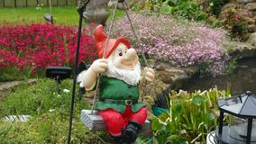 Happy gnome on a swing. Stock Photography