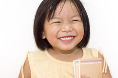 Happy going to school. A cute Asian girl happy with her books royalty free stock photos