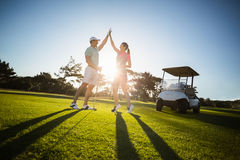 Happy golf player couple giving high five Stock Photo