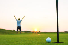 Happy golf player on a golf court at sunset Stock Photos