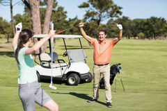 Happy golfer couple with arms raised Royalty Free Stock Photography