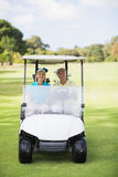 Happy golfer couple sitting in golf buggy Royalty Free Stock Images