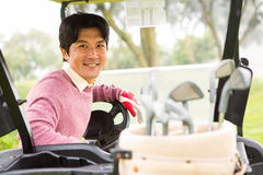 Happy golfer driving his golf buggy smiling at camera Stock Images